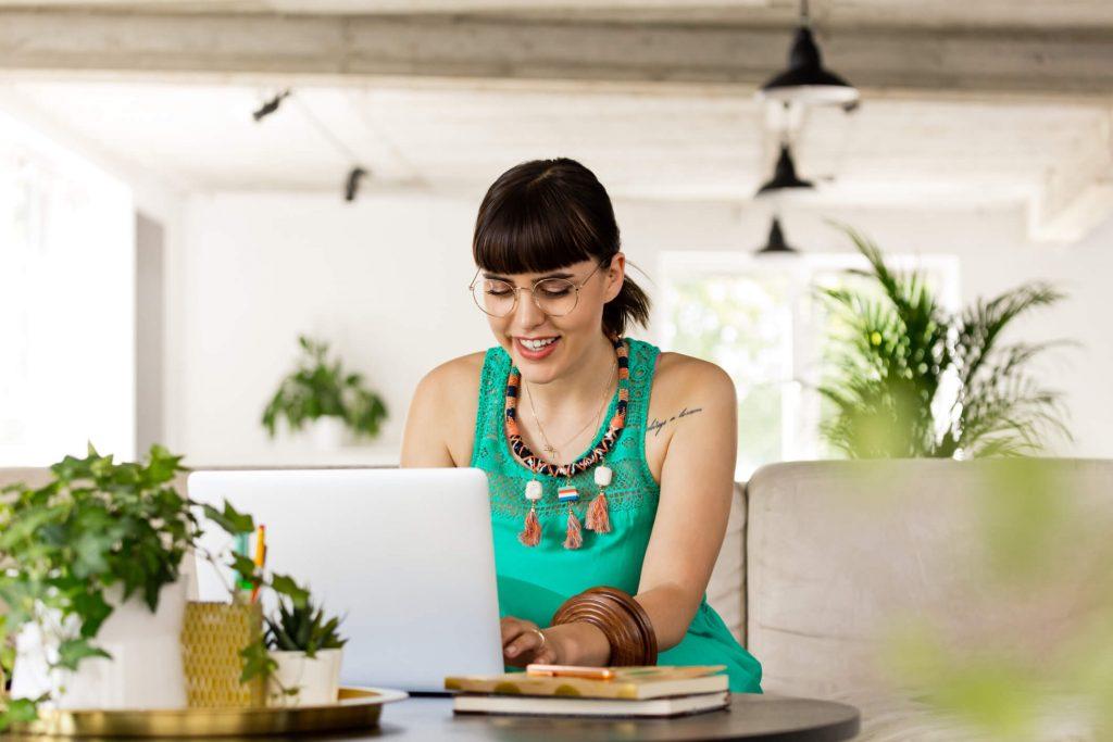 Kobieta ubrana w stylu boho siedząca przy laptopie