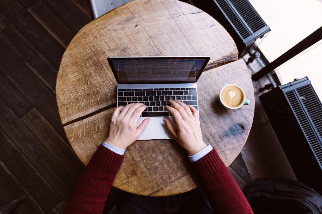 Dłonie, laptop i kawa na okrągłym drewnianym stoliku