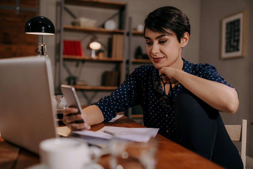 Uśmiechnięta kobieta patrząca w telefon